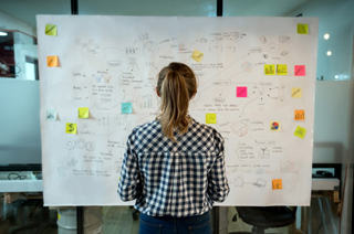 woman in front of large paper filled with notes and post its